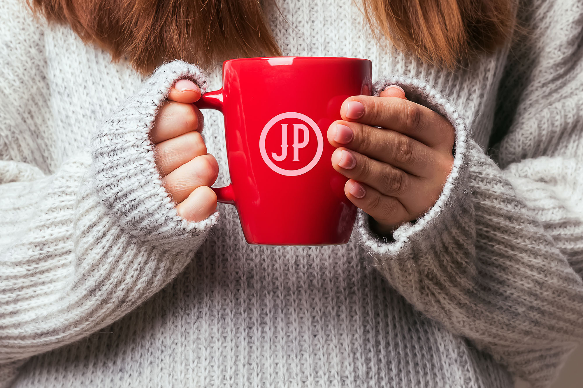 Picture of a woman's hands holding a red coffee mug