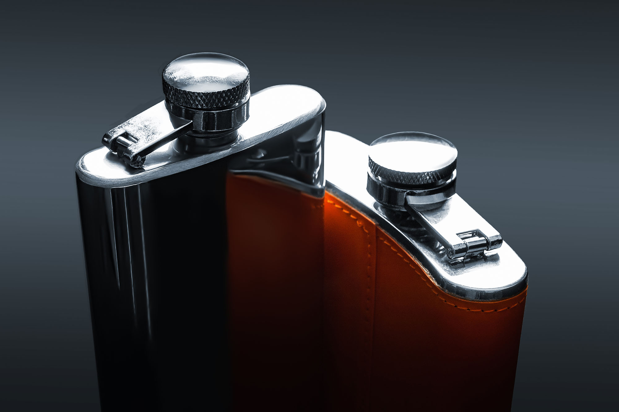 Two flask for alcohol. Top view of steel flasks with leather trim on a black background. Tanks for whiskey, rum, vodka and various alcohol. Lifestyle and travel.